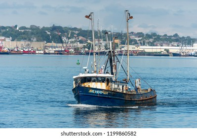 New Bedford, Massachusetts, USA - September 15, 2018: Commercial fishing vessel Silverfox, hailing port Cape May, New Jersey, under way with New Bedford waterfront in background