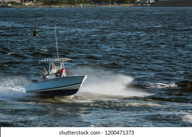 New Bedford, Massachusetts, USA - September 5, 2018: Passengers ducking for cover as powerboat flies through wind-driven chop on Acushnet River in early evening