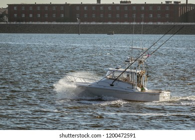 New Bedford, Massachusetts, USA - September 5, 2018: Sport fishing boat Wild Horses crashing through evening chop in New Bedford outer harbor with mill in background