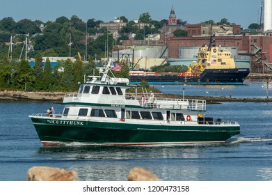 New Bedford, Massachusetts, USA - September 5, 2018: Ferry Cuttyhunk crossing Acushnet River with supply ship Commander and New Bedford waterfront in background