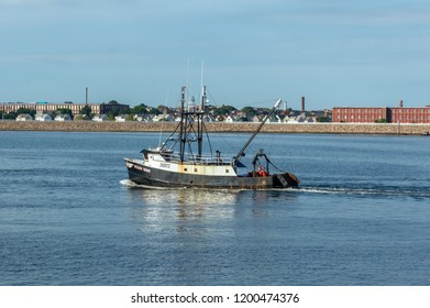 New Bedford, Massachusetts, USA - September 5, 2018: Commercial fishing boat Ocean Wave, hailing port Cape May, New Jersey, crossing New Bedford outer harbor with mills and residences in background