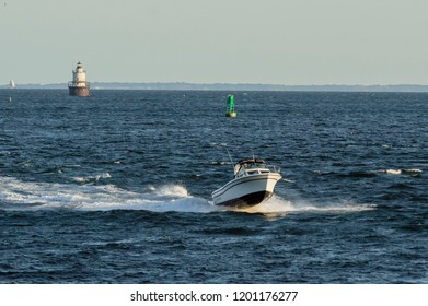 New Bedford, Massachusetts, USA - September 5, 2018: Powerboat flying over choppy waves in New Bedford outer harbor with lighthouse in background
