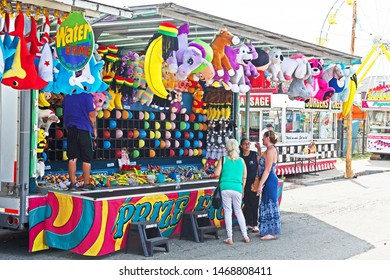 New Bedford, Massachusetts/USA - August 2 2019: three women examine the brightly colored side show featuring a water game at the  Feast of the Blessed Sacrament in New Bedford.