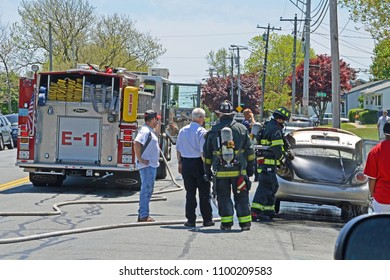New Bedford, Massachusetts/USA - May 19 2012: New Bedford firemen extinguish a blaze in a car trunk.