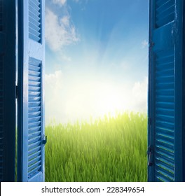 new beginings concept  - open blue door to grass and sky with sunshine