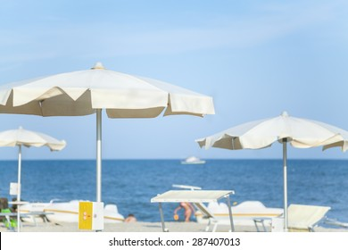 New beige parasols on the fashionable sea beach sunny summer day
