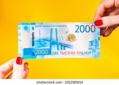 A new bill of two thousand rubles in the hands of the girl. Banknote in 2000 rubles in female hands. The girl is considering new money for Russia.