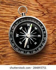 New black compass  on wood in closeup