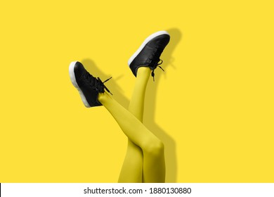 New Black female sneakers on long slender woman legs in yellow tights isolated on yellow background. Monochrome pop art concept.