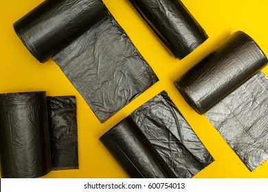 New black garbage bags on a yellow background.