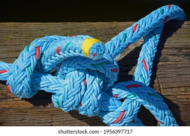 New blue marina rope tied to boat moorage.