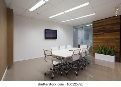 New board room with table, chairs and plasma display.