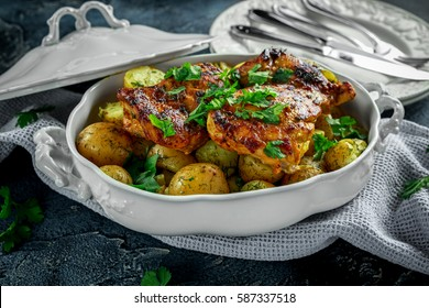 New boiled potatoes with dill and butter served with baked skinless boneless chicken thighs in vintage casserole