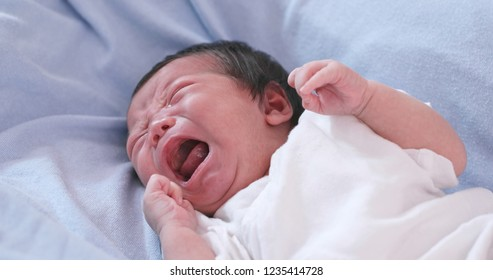 New born baby crying on bed