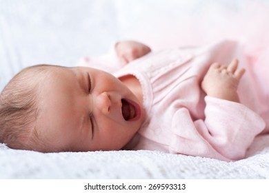 new born baby lying on texture blanket, yawning, light pink dress, looking at camera