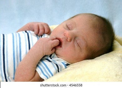 New born baby sleeping with his finger in his mouth