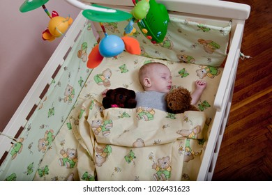 New born child in wooden co-sleeper crib. Infant sleeping in bedside bassinet. Safe co-sleeping in a bed side cot. Little boy taking a nap under knitted blanket. Top view