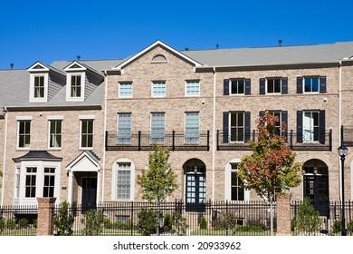 A new brick condominium complex behind an iron fence against blue sky
