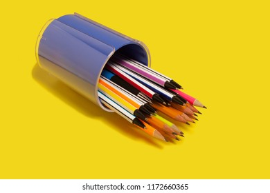 new bright colored pens lying in a purple penholder on a yellow background. concept of office supplies. free copyspace