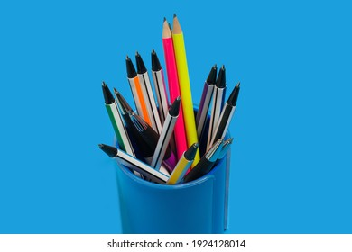 neue, helle Stifte und Stifte, die auf blauem Hintergrund in einem Stift liegen. Konzept der Bürobedarf. Freiraum für Werbetext