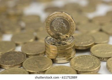 New British one pound sterling coin alongside the old one pound coins up close macro studio shot against a shiny reflective White background