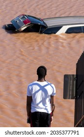 New Brunswick, New Jersey - September 2, 2021: Young man views flood water and abandoned vehicle in the aftermath of Tropical Storm Ida.