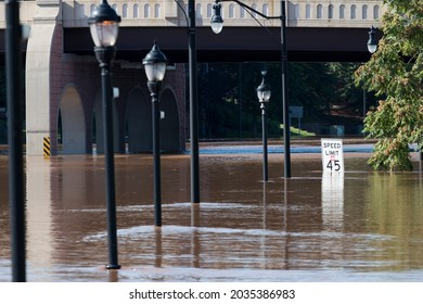 New Brunswick, New Jersey - September 2, 2021: Highway lampposts and street sign nearly completely submerged in flood water, in the aftermath of Tropical Storm Ida.