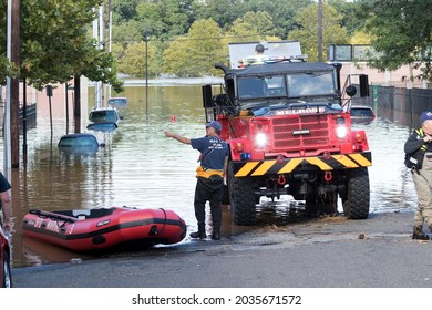 New Brunswick, New Jersey - September 2, 2021: Service workers and rescue teams with service trucks and inflatable rafts, in the aftermath of Tropical Storm Ida.