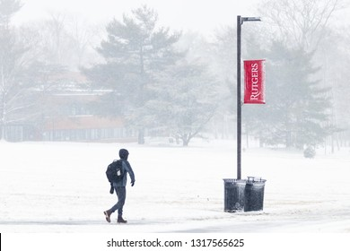 New Brunswick, NJ - February 12, 2019:  Rutgers University banner in a storm of snow, sleet, and frozen rain; student on campus in foreground.
