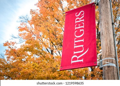 New Brunswick, NJ - November 2, 2018: Rutgers University logo flag with backdrop of colorful maple tree leaves turning gold and red in autumn.
