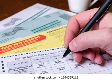 New Brunswick, NJ - October 28, 2020: Hand holding pen, preparing to fill out official mail-in ballot for 2020 US General Election.