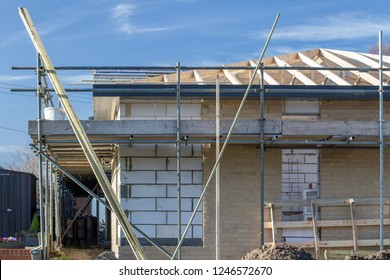 New build bungalow under construction. Building homes for the growing elderly population. Scaffolding surrounding a partially brick built house with exposed roof trusses and breeze block walls.