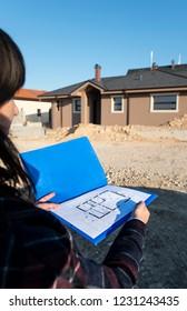 New build house and blueprints. Construction site