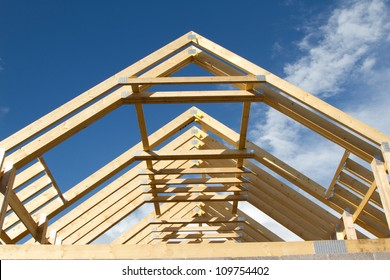 A new build roof with a wooden truss framework making an apex against a blue sky with cloud.