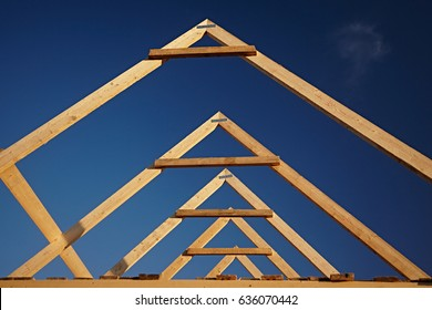 A new build roof with a wooden truss framework making an apex against a blue sky. Frame House Construction.