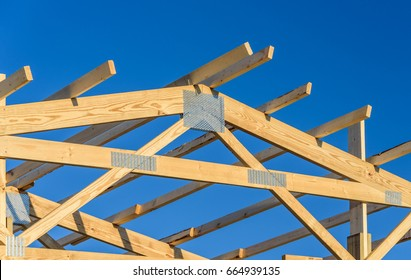 A new build roof with a wooden truss framework with a blue sky background.