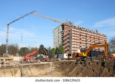 new building construction site with workers cranes and excavator