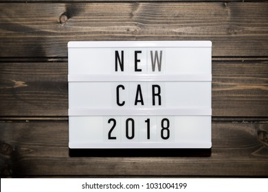 new car 2018 message in light box, grunge wood table flat lay shot from above
