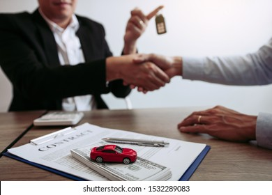 New car buyers and car salesmen are shaking hands to make agreements about car sales.