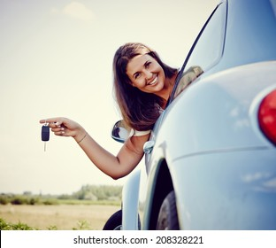 New car - driver woman Holding Her new Car keys out of the window, smiling looking into Camera. More of Her: