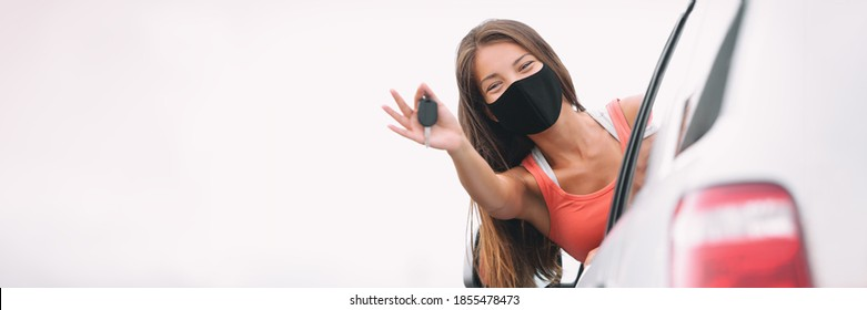 New car happy Asian driver woman wearing face mask for coronavirus showing keys with pride. Drivers license concept panoramic banner.