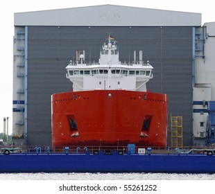 new Cargo ship in front of a shipyard hall