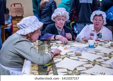 New Carlisle Indiana USA March 17, 2019 ; at the  Bendix wood sugar camp days event, women in old fashioned costumes hold a quilting bee at this fun demonstration
