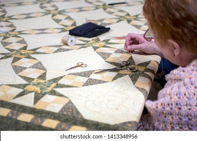 New Carlisle IN USA, March 17 2019;   During the Bendix woods sugar camp days, a woman works on a decorative quit during an old fashioned quilting bee demonstration