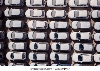 New cars covered in protective white sheets parked in a holding platform - Aerial image