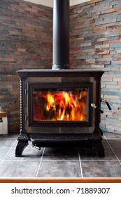 A new cast iron wood stove burning hot with slate tile.