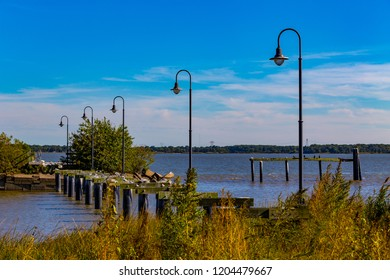 New Castle, DE, USA - September 23, 2015: Remains of a damaged dock and pier stands in the Delaware River.