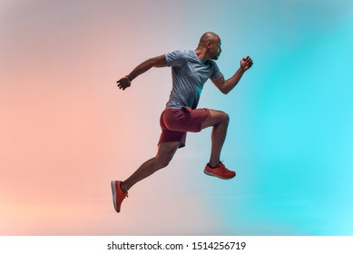 New champion. Full length of young african man in sports clothing jumping against colorful background