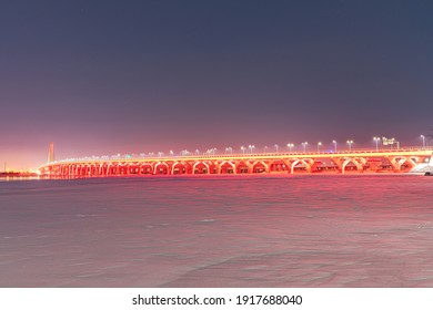 New Champlain Bridge illuminated in red for Valentine's Day in Montreal, Quebec, Canada. Red reflections can be seen on the St-Lawrence river in winter with snow and ice all around.