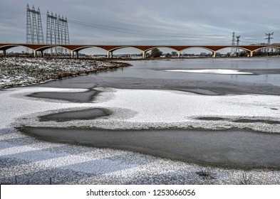 The new channel of the river Waal near Nijmegen, the Netherlands, partly covered with ice and snow, with city bridge De Oversteek (The Crossing) in the background